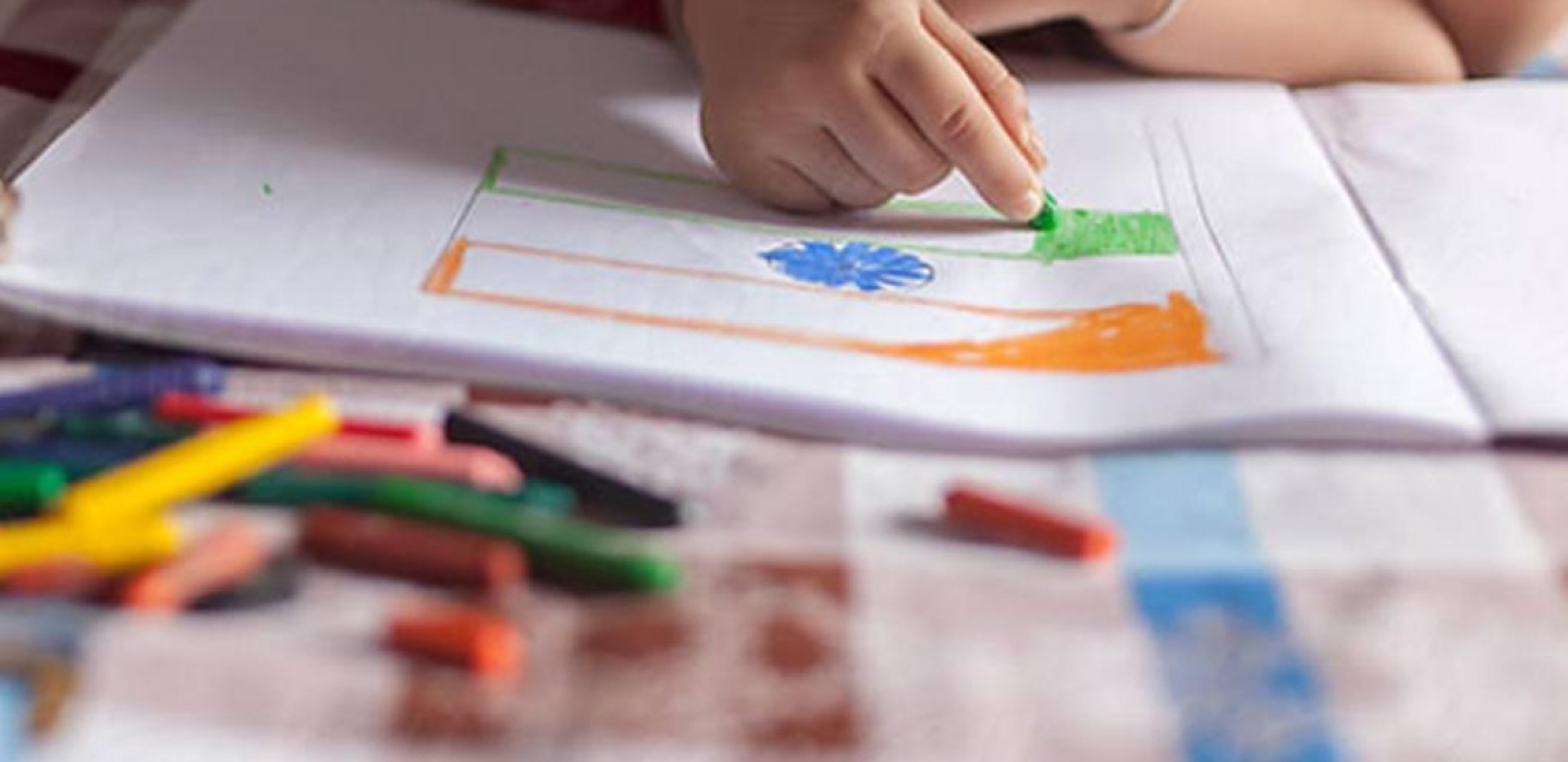 A child is using crayons to draw
